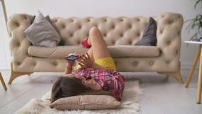 Frau, die intelligentes Telefon beim Lügen auf dem Boden verwendet stock footage