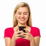 Frau, die intelligentes Telefon über weißem Hintergrund verwendet Stockbild