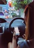 Frau, die intelligentes Telefon im Auto verwendet Stockbilder