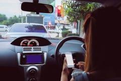 Frau, die intelligentes Telefon im Auto verwendet Lizenzfreies Stockfoto
