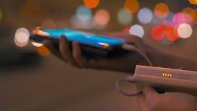 Frau, die intelligentes Telefon mit Energiebank auflädt stock video