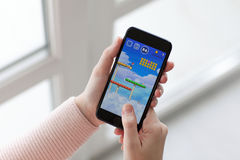 Frau, die iPhone 7 Jet Black-Spiel Super-Mario Run hält Lizenzfreie Stockbilder