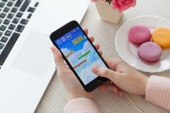 Frau, die iPhone 7 Jet Black-Spiel Super-Mario Run hält Stockfoto
