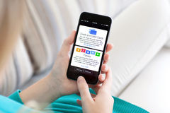 Frau, die iPhone 6 mit Apple-Lohn und -sparbuch hält Stockfoto
