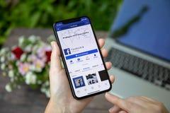Frau, die iPhone X mit Social Networking-Service Facebook hält Stockfoto
