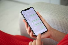 Frau, die iPhone X mit Social Networking-Service WhatsApp hält lizenzfreie stockfotografie