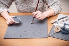 Frau, die irgendein Handwerk verziert Gewebe und Farbe Stockfotografie
