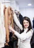 Frau, die Jacke am Bekleidungsgeschäft wählt Stockbild