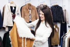 Frau, die Jacke an der Butike wählt Lizenzfreie Stockfotografie