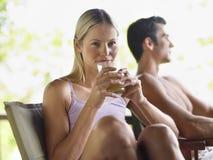 Frau, die Juice By Shirtless Man trinkt stockbilder