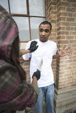 Frau, die jungen Mann mit Messer erschrickt Stockbild