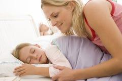 Frau, die junges Mädchen beim Bettlächeln aufweckt Stockfotografie