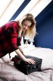 Frau, die kämpft, um Koffer zu schließen lizenzfreies stockfoto
