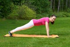 Frau, die Körper in der Planke parallel zum Boden zu den geraden Händen auf Matte hält Stockbild