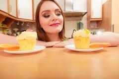 Frau, die köstlichen süßen Kuchen betrachtet gluttony lizenzfreies stockbild