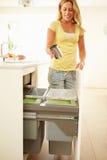 Frau, die Küchen-Abfall im Behälter aufbereitet Stockbild