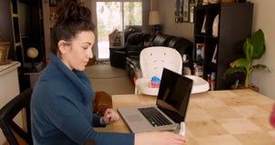 Frau, die am Küchentisch unter Verwendung des Laptops sitzt stock footage
