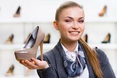 Frau, die Kaffee-farbigen auf den Fersen gefolgten Schuh hält Lizenzfreie Stockfotografie
