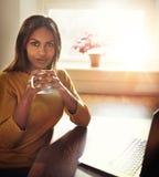 Frau, die Kaffee hält, während Sie nahe Fenster gesetzt werden Lizenzfreie Stockfotografie