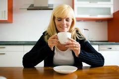 Frau, die Kaffee zum Frühstück trinkt Lizenzfreie Stockbilder
