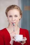 Frau, die Kaffeetasse beim Lecken des Löffels hält Lizenzfreie Stockbilder