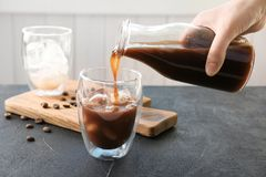 Frau, die kalten Gebräukaffee in Glas gießt stockbilder