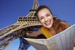 Frau, die Karte hält und vor Eiffelturm, Paris zeigt Stockfoto