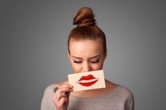 Frau, die Karte mit Kusslippenstiftkennzeichen auf Steigungshintergrund hält Stockfoto