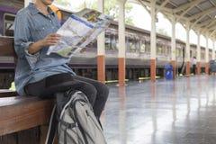 Frau, die Karte mit Rucksack an der Bahnstation hält Stockfotografie