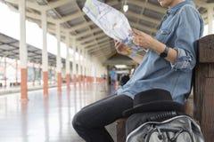 Frau, die Karte mit Rucksack an der Bahnstation hält Stockbild
