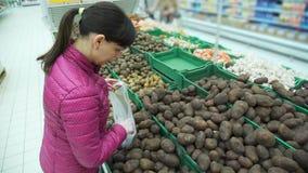 Frau, die Kartoffel in eine Tasche in einem Supermarkt setzt stock video footage
