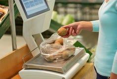 Frau, die Kartoffeln auf Skala am Gemischtwarenladen wiegt Stockfotografie