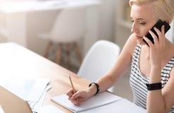 Frau, die Kenntnisse nimmt und auf Smartphone spricht Lizenzfreie Stockfotos