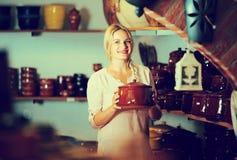 Frau, die keramisches Gerät wählt stockfotografie
