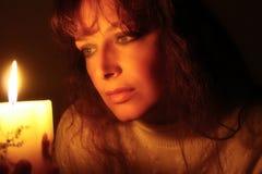 Frau, die Kerzenlicht untersucht stockfotos