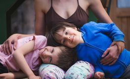 Frau, die Kinder auf der Terrasse eines Holzhauses umarmt stockfotografie