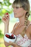 Frau, die Kirschen isst Lizenzfreie Stockfotografie