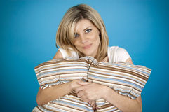 Frau, die Kissen umarmt lizenzfreie stockbilder