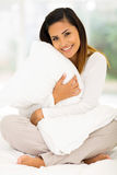 Frau, die Kissen umarmt Stockfotografie