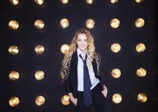 Frau, die klassischen Anzug über goldenem glänzendem Hintergrund trägt Lizenzfreies Stockbild