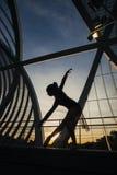 Frau, die klassisches Ballett auf einer Brücke an der Dämmerung tanzt Stockfoto