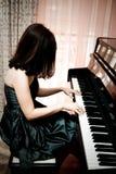 Frau, die Klavier spielt Stockbild