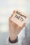 Frau, die klebende Anmerkung mit Halloween-Parteitext hält Stockbilder