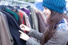 Frau, die Kleidung an der Flohmarkt wählt. stockbild
