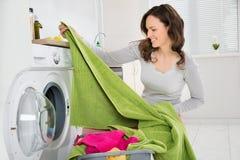 Frau, die Kleidung in der Waschmaschine wäscht stockbilder