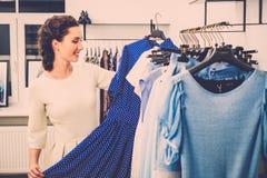 Frau, die Kleidung in einem Ausstellungsraum wählt Stockfoto