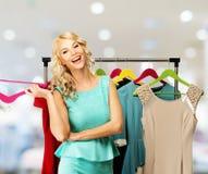 Frau, die Kleidung in einem Einkaufszentrum wählt Stockbild