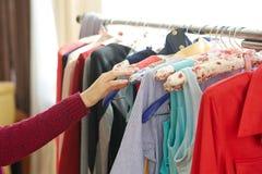 Frau, die Kleidung im Shop vorwählt Stockfotos