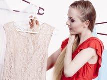 Frau, die Kleidung im Shop wählt Lizenzfreies Stockfoto