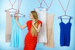 Frau, die Kleidung im Shop wählt Lizenzfreie Stockfotos